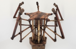 This stool points towards an occupant when the weight of a person rests on the seat.  The five finger mechanisms extend and rise from beneath the seat when depressed.  Once weight is released, springs pull the fingers down to their starting position and the seat raises back up. In this image the stool is arranged as if someone is seated.
